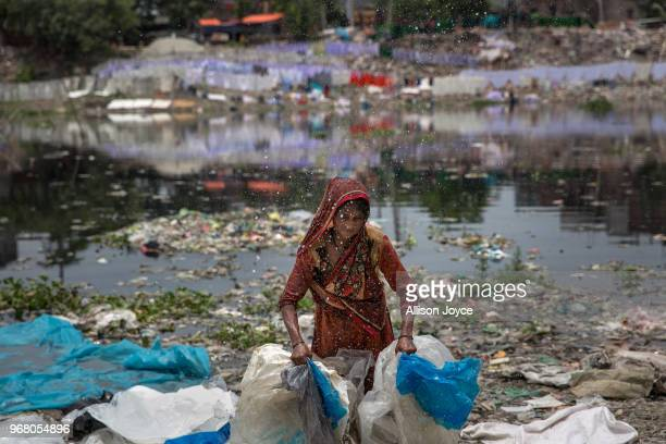 A woman washes plastic in a canal that leads to the Buriganga river on June 3 2018 in Dhaka Bangladesh Bangladesh has been reportedly ranked 10th out...