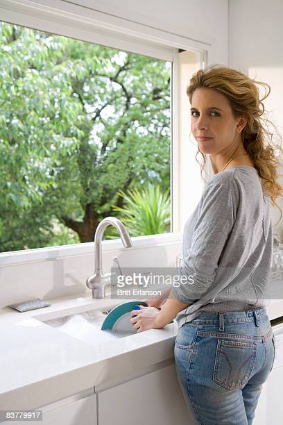 Woman washes plate at sink