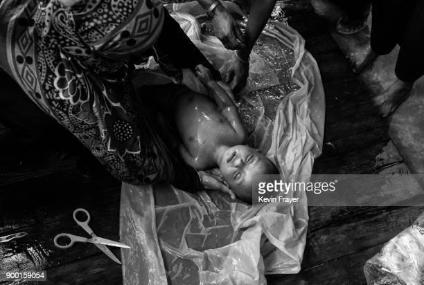 COX'S BAZAR BANGLADESH SEPTEMBER 29 A woman washes the body of a young Rohingya refugee child prior to burial after a boat capsized killing dozens...