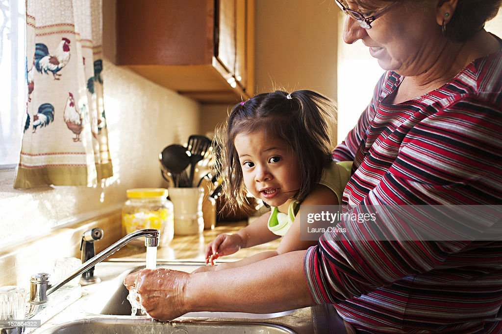 Woman washes toddler hands at kitchen sink : Stock Photo