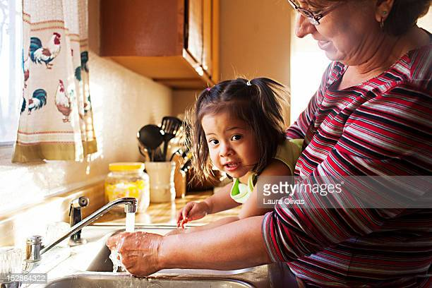 woman washes toddler hands at kitchen sink - mid section stock photos and pictures