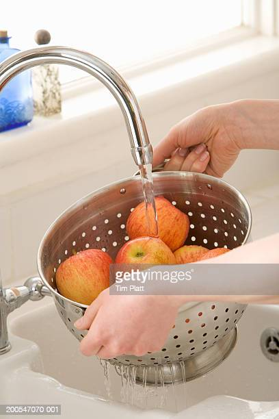 Woman washing apples in kitchen sink, close-up, elevated view
