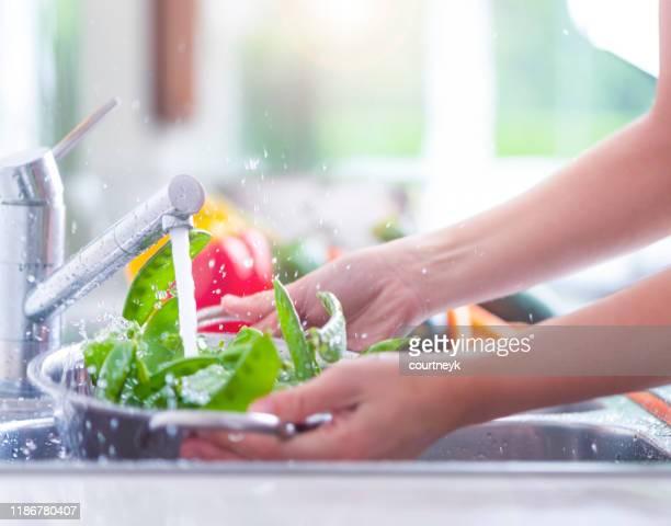 流しのザルで明るい緑色の雪エンドウを洗う女性。 - 洗う ストックフォトと画像