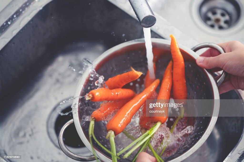 Woman washing carrots in the sink. : Stock Photo