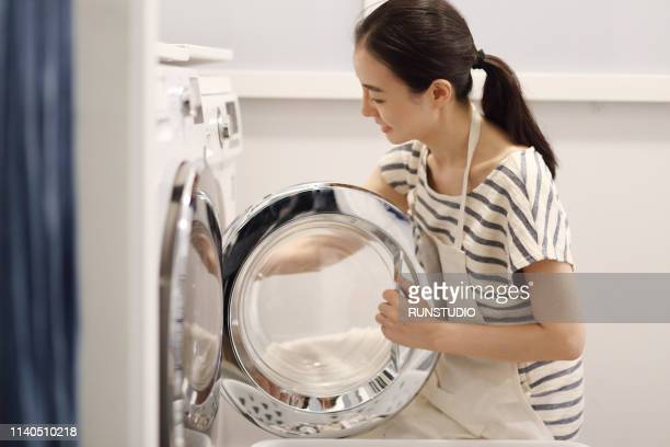 woman washing cloth with washing machine - homemaker stock pictures, royalty-free photos & images