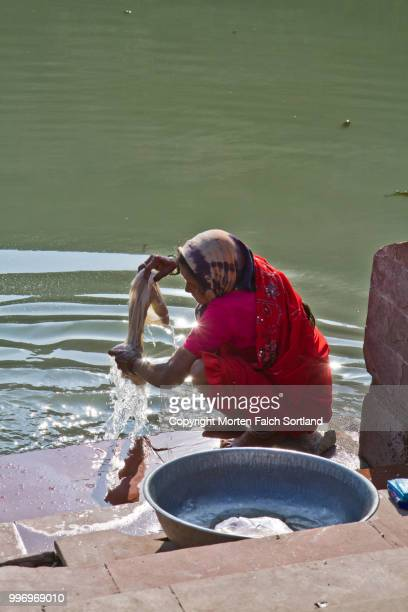 Woman washing clothes in lake