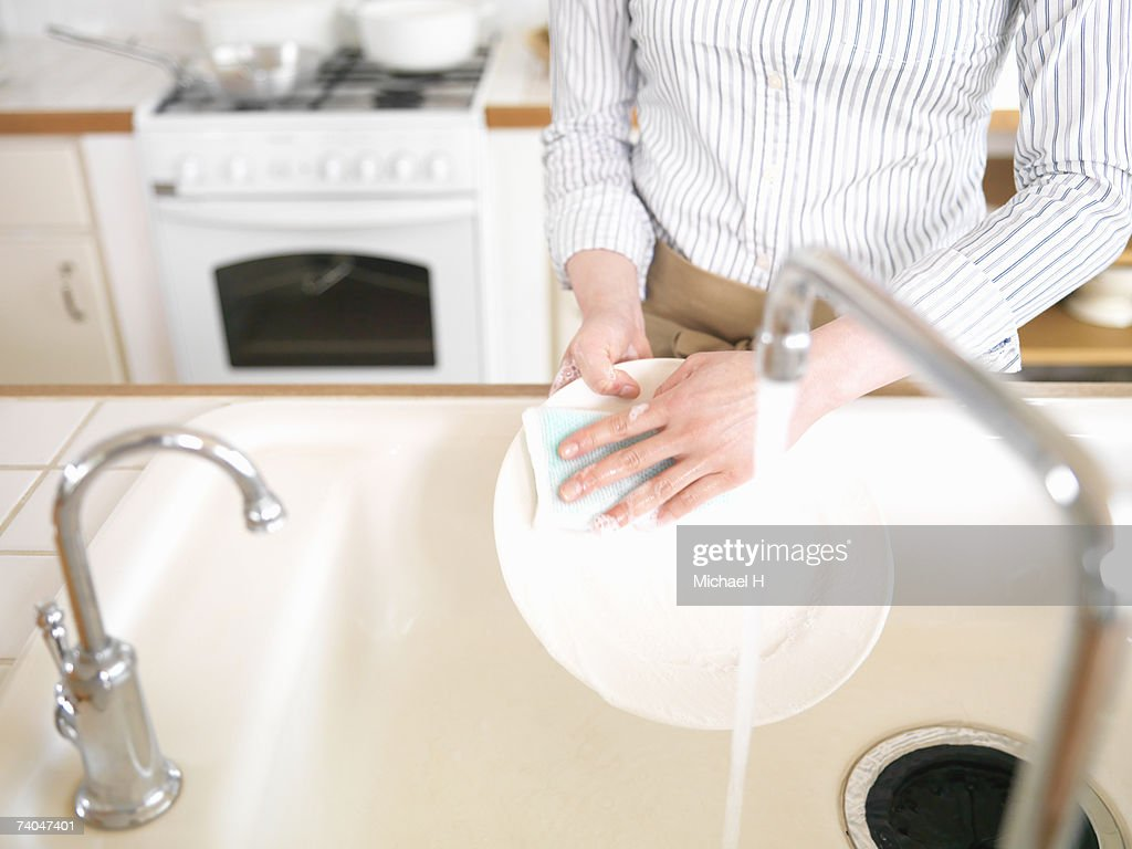 Woman washing dishes in kitchen, mid section, elevated view : ストックフォト