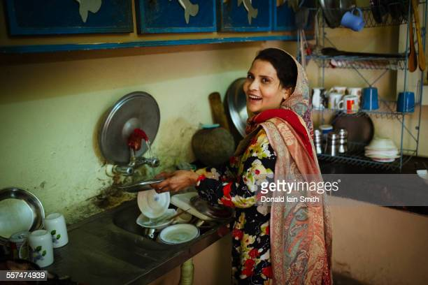 woman washing dishes in kitchen - punjab pakistan stock photos and pictures