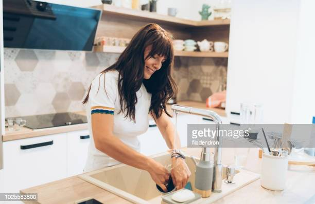 woman washing dishes - dishwashing liquid stock photos and pictures