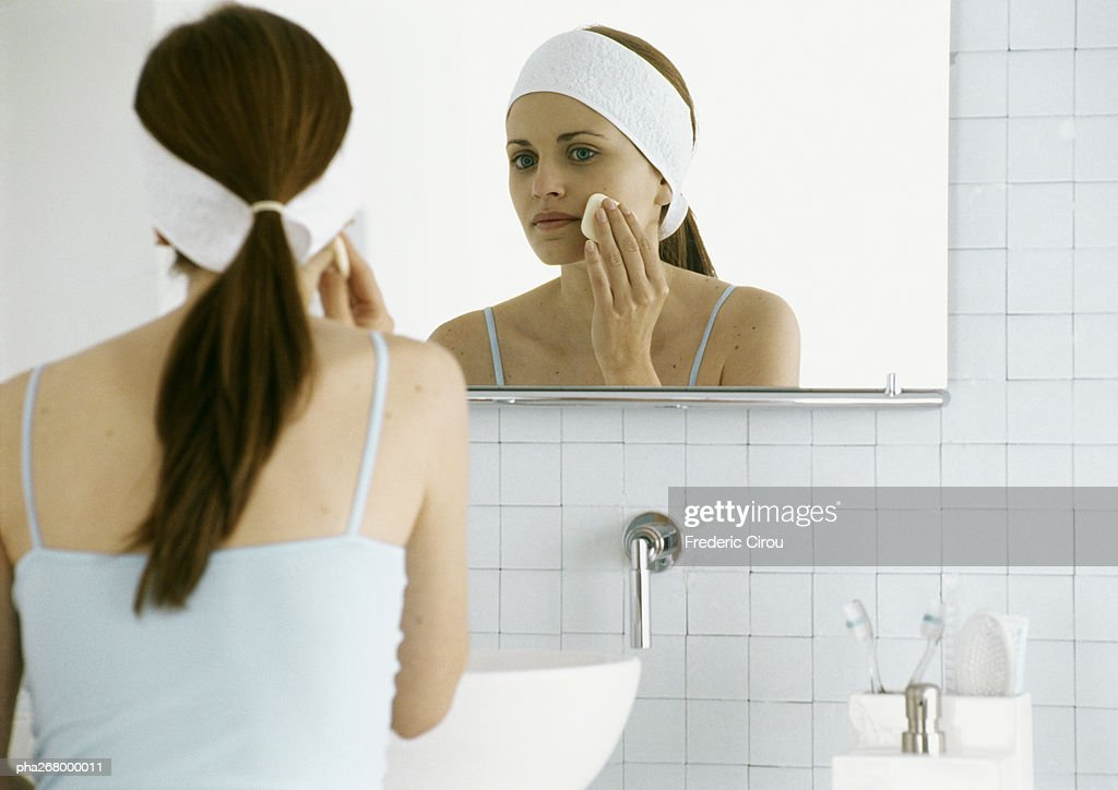 Woman washing face in front of mirror : Stockfoto