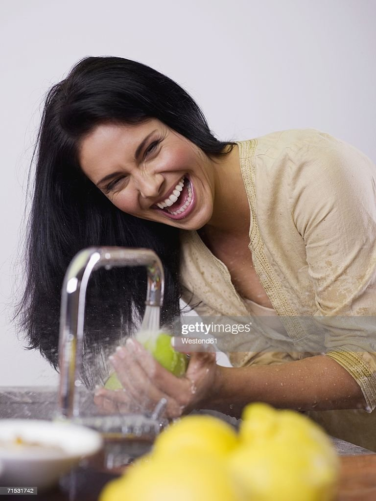 Woman Washing Fruit At Kitchen Sink Laughing High Res Stock Photo Getty Images