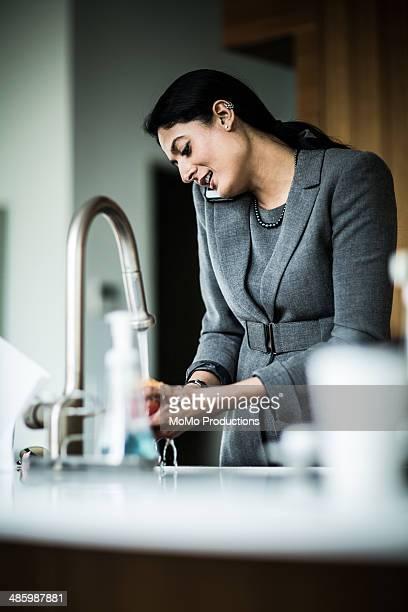 woman washing fruit in sink