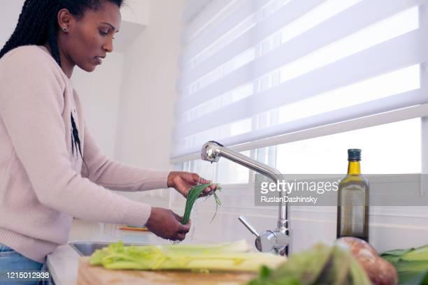 donna che lava la cipolla verde sotto l'acqua del rubinetto. - cipollina foto e immagini stock