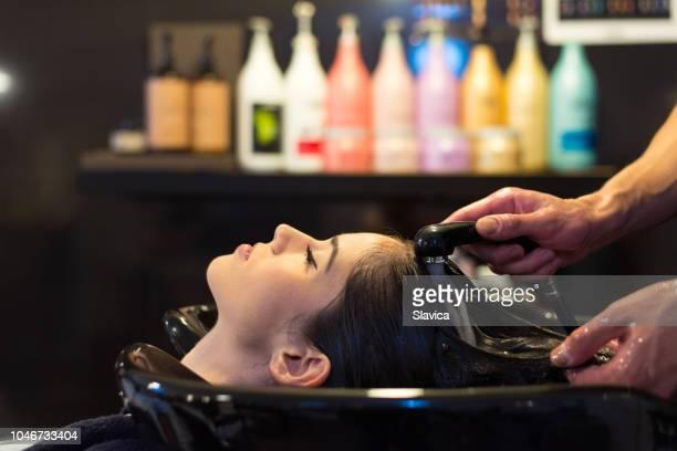 donna che lava i capelli nel parrucchiere - hair stylist foto e immagini stock