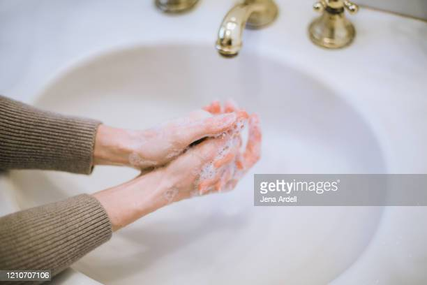 woman washing hands, hand washing due to health anxiety and ocd - foam finger - fotografias e filmes do acervo