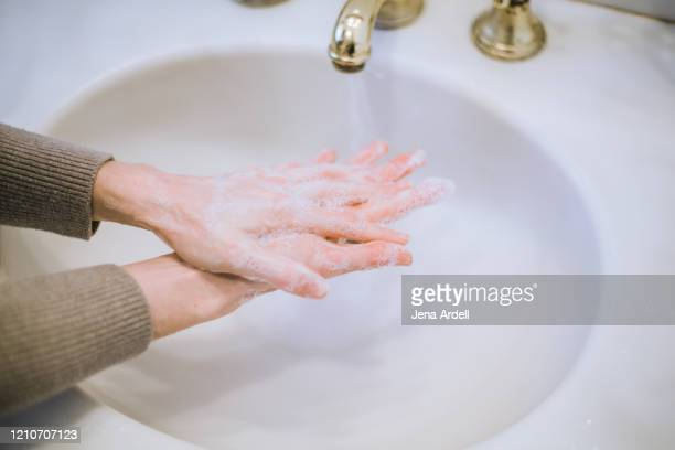 woman washing hands, in between fingers, good hygiene, preventing spread of germs, bacteria and viruses - foam finger - fotografias e filmes do acervo
