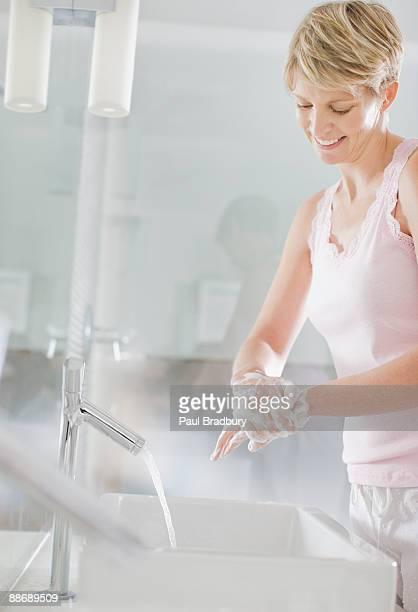 femme se laver les mains dans la salle de bains - lavage des mains photos et images de collection