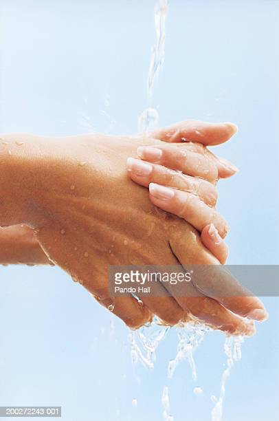 Woman washing hands under running water, close-up