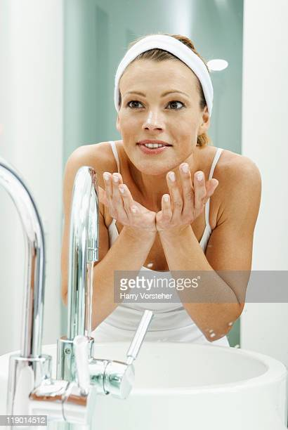 Woman washing her face in bathroom