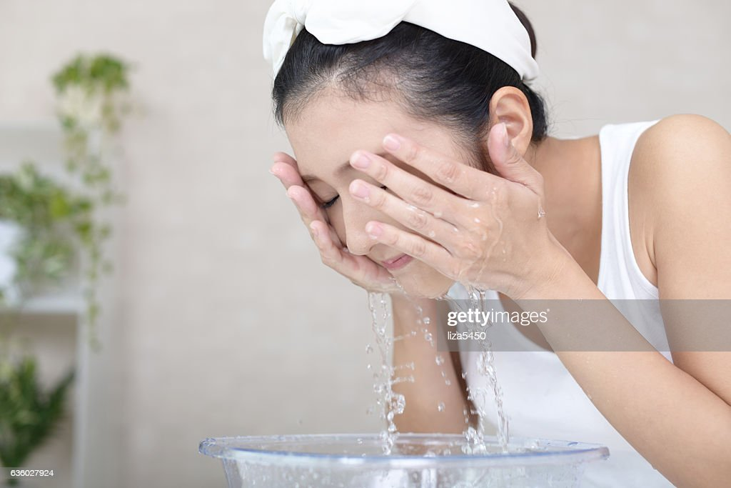 Woman washing her face : Stock Photo