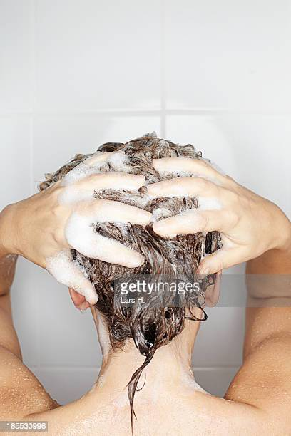 woman washing her hair in shower - shampoo stock-fotos und bilder