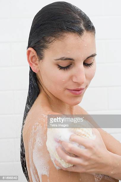 woman washing in shower - loofah stock photos and pictures