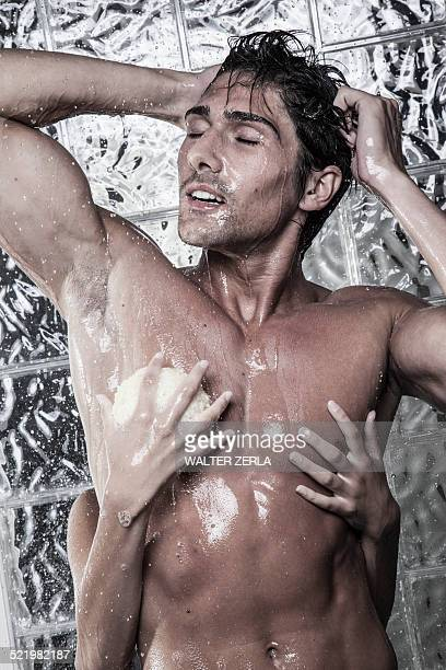Woman washing man from behind in shower