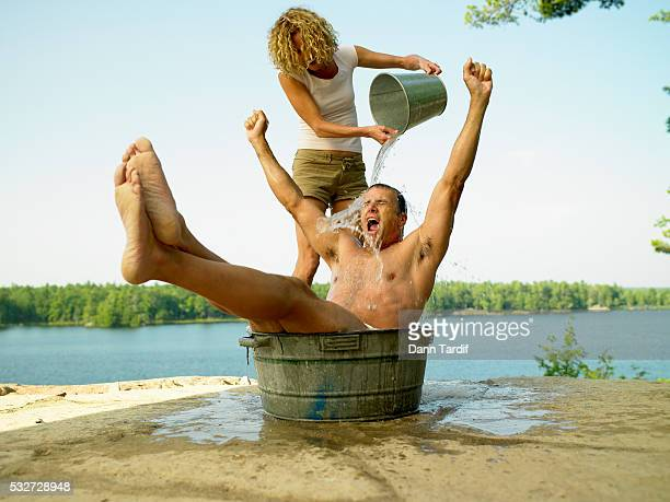 Woman Washing Man in Outdoor Tub