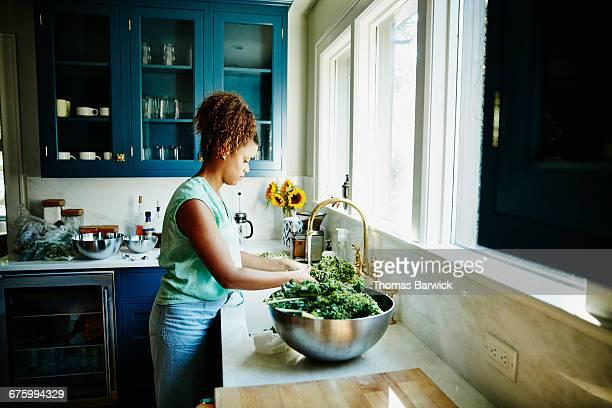 Woman washing organic kale in kitchen sink