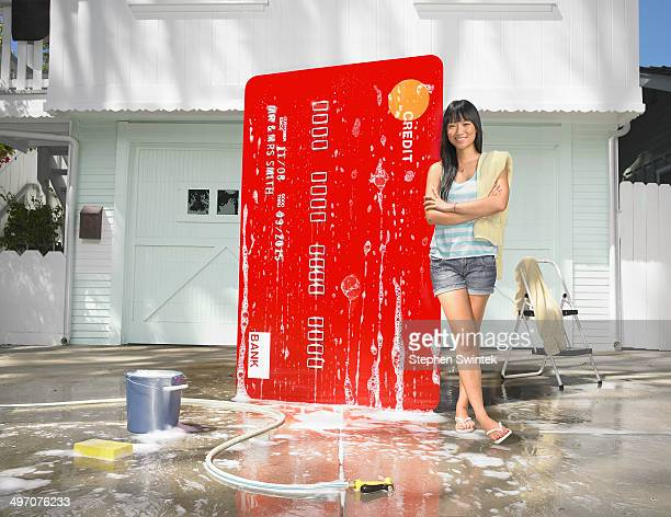 Woman washing oversized credit card in driveway