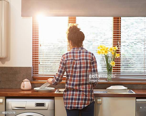Woman washing up crockery in kitchen.