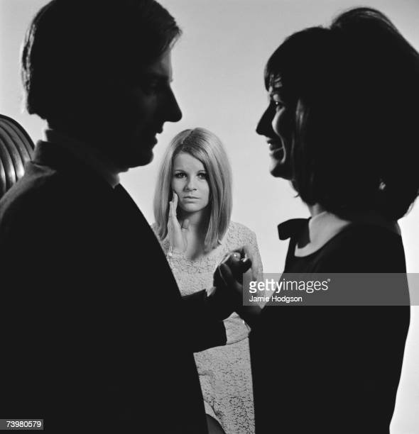 A woman watches a happy couple with sadness and envy circa 1965