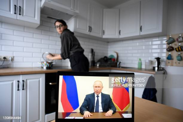 Woman watches a live broadcast of Russian President Vladimir Putin's address to the nation over the coronavirus while cooking in an appartment, in...