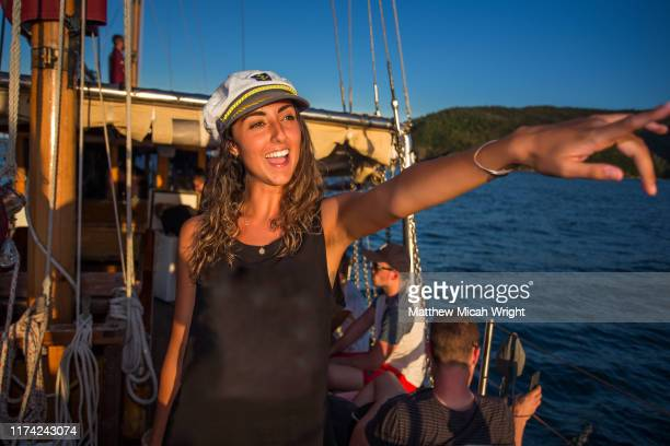 a woman watches a sunset from a sailboat in the whitsundays. - セーラーハット ストックフォトと画像