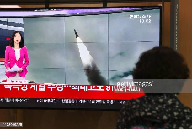 TOPSHOT A woman watches a television news screen showing file footage of a North Korean missile launch at a railway station in Seoul on October 2...