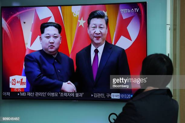 A woman watches a television screen showing a news broadcast featuring North Korean Leader Kim Jong Un during a meeting with China's president Xi...