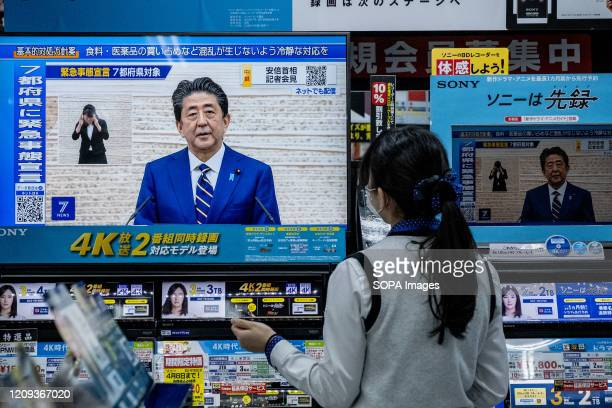 Woman watches a TV as the Japanese Prime Minister Shinzo Abe speaks at a press conference and addressing the citizen through TV. Prime Minister...