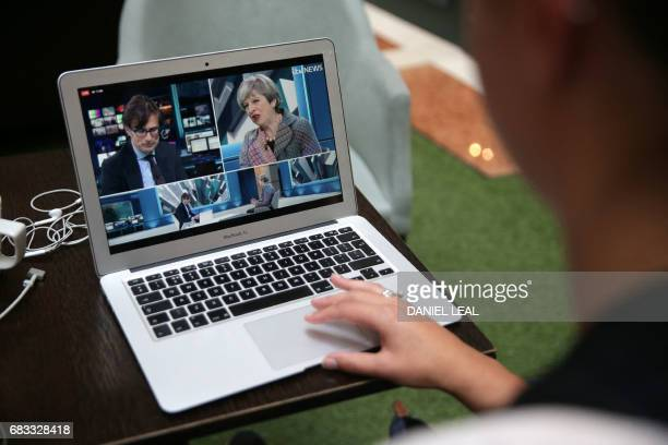 A woman watches as British Prime Minister Theresa May takes part in a Question and Answer session on ITV news via their social media Facebook...