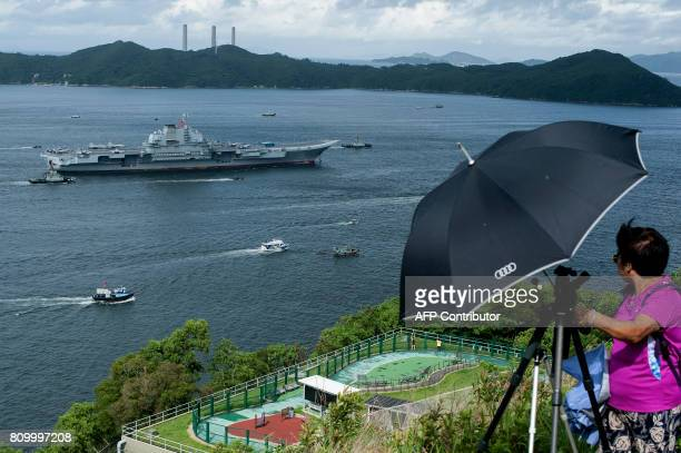 Woman watches as China's aircraft carrier Liaoning sails into the waters of Hong Kong on July 7, 2017. China's national defence ministry had said the...