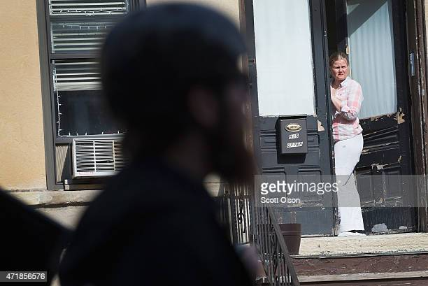 A woman watches as demonstrators participating in a May Day march pass by her home on May 1 2015 in Chicago Illinois The demonstration was one of...