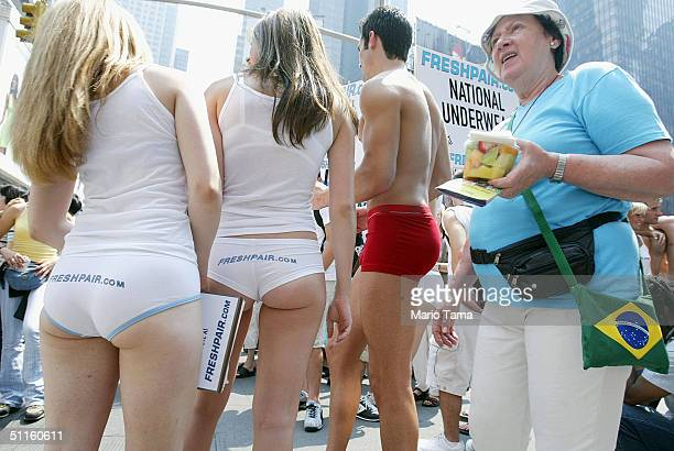 A woman watches as Freshpaircom models stand in their underwear in Times Square on the unofficial National Underwear Day August 11 2004 in New York...