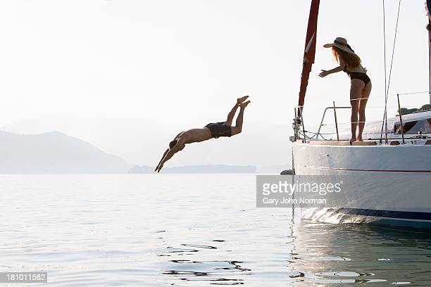 woman watches as man dives off yacht