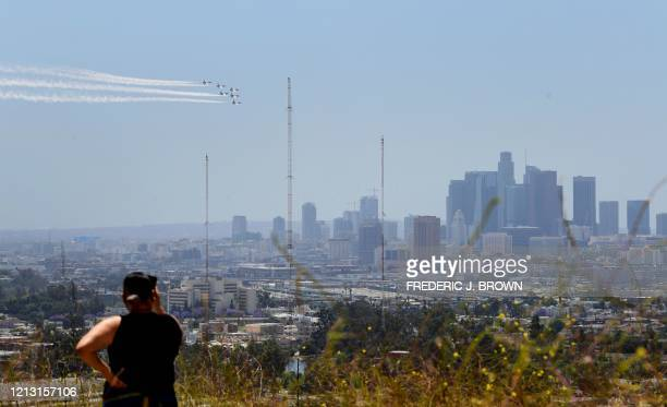 A woman watches as the US Air Force Thunderbirds fly over Los Angeles California on May 15 2020 as a salute to frontline COVID19 workers and first...