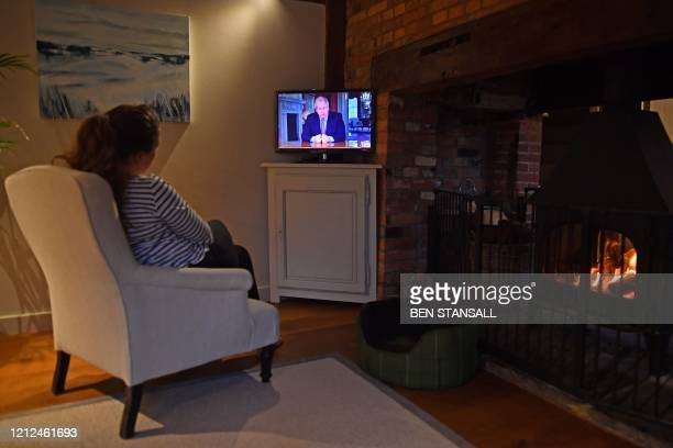 Woman watches Britain's Prime Minister Boris Johnson give a televised message to the nation in Brenchley, south east England on May 10 as the...