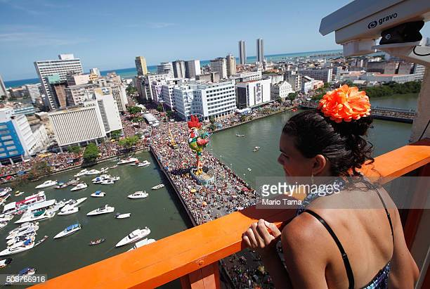 A woman watches Carnival celebrations from a hotel rooftop on February 6 2016 in Recife Pernambuco state Brazil Officials say as many as 100000...