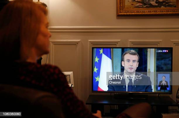 A woman watches French television as the French President Emmanuel Macron delivers a speech to the nation from the Elysee Presidential Palace on...