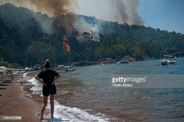 Woman watches from a beach the forest burning on August 3, 2021 in Mugla, a Marmaris' district, as Turkey struggles against its deadliest wildfires...