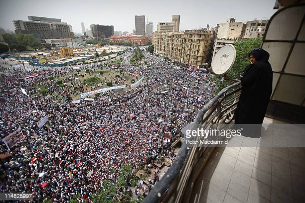 A woman watches from her balcony as demonstrators gather in Tahrir Square on May 27 2011 in Cairo Egypt The ruling Supreme Council of the Armed...