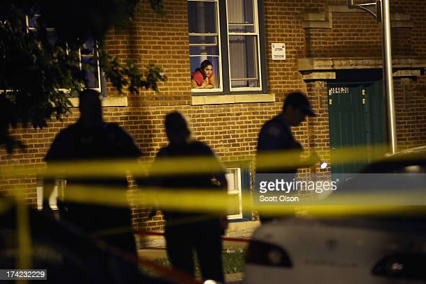 A woman watches from her window as police look for evidence after 20yearold Carlos Barron was shot and killed in the Humboldt Park neighborhood on...