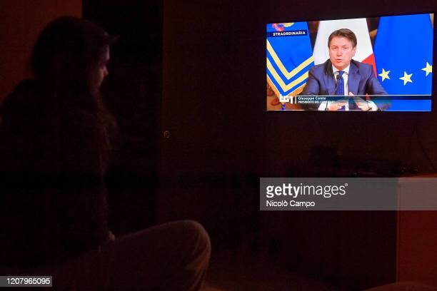 A woman watches Italian Prime Minister Giuseppe Conte on TV announcing the closure of any production activity not strictly necessary to guarantee the...
